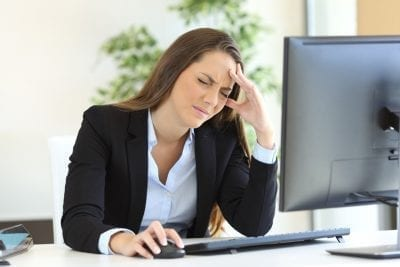 woman in front of computer search for ways to cure migraines