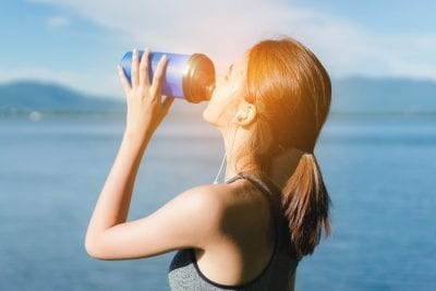 woman drinking water to cure migraines