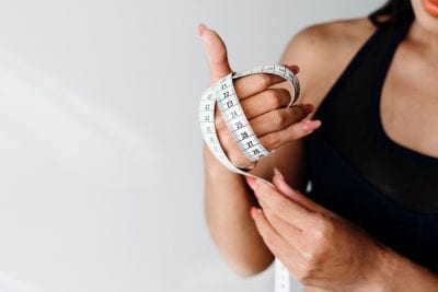 woman with fast metabolism holding tape measure