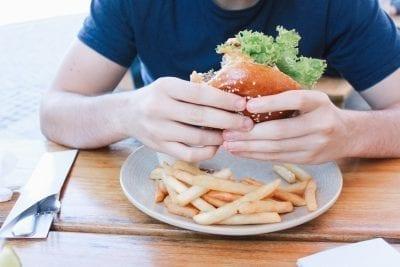 man holding hamburger poor diet constipation