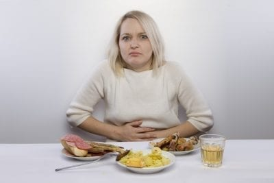 woman in front of food suffering from constipation