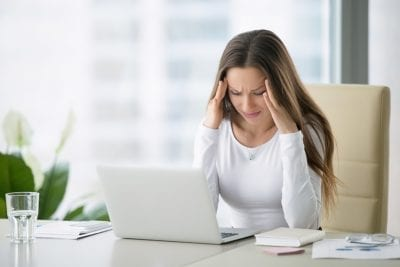 woman with hormone imbalance in front of laptop