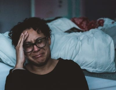 woman crying beside her bed because of stress and menopause