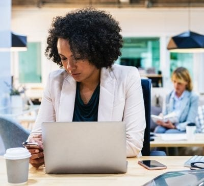 woman looking at her laptop reading about menopause