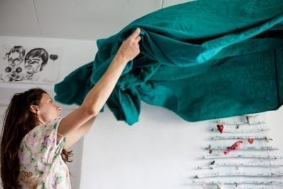 woman holding blanket, cleaning, checking for mold exposure