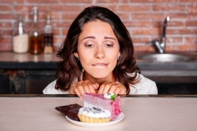 woman having food cravings looking at cake, chocolate on the table
