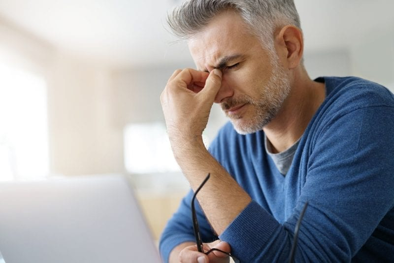 man suffers from adrenal fatigue holding his eye glass, laptop