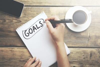 woman writing, setting better goals, habit change