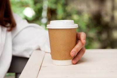 woman holding paper cup with coffee, gluten-free diet