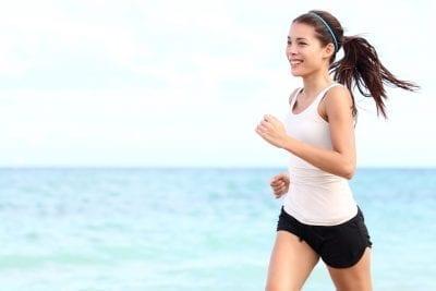 woman running on seashore under the sun, boost metabolism naturally