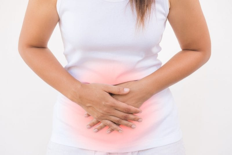 woman holding her tummy, looking for best ways to heal leaky gut