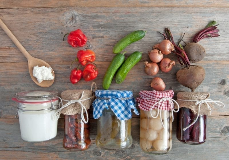 different kinds of fermented foods in jars including kefir, gherkins and peppers and onions, probiotics,